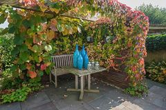 O jardim que a tabela ajustada é coberta com é decorado com vaso azul Fotos de Stock Royalty Free