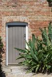 O jardim secreto Porta de madeira fechado em uma parede do vermelho-tijolo Fotos de Stock Royalty Free