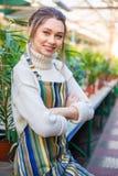 O jardineiro bonito da mulher que está com mãos dobrou-se na estufa Imagem de Stock Royalty Free