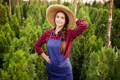 O jardineiro de encantamento da menina em um chapéu de palha está no berçário-jardim com muitos thujas em um dia ensolarado morno foto de stock
