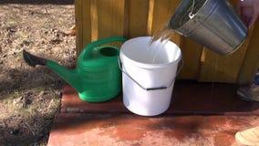 O jardineiro derrama a água na cubeta plástica filme