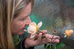 O jardineiro fêmea louro na prima dos anos, cheiros satisfeitos com os olhos fechados nas rosas de vermelho do aroma do perfume f imagem de stock royalty free