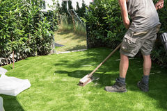 O jardineiro profissional põe a areia sobre o relvado artificial Fotografia de Stock