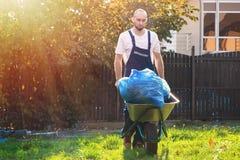 O jardineiro rola um carro com os sacos das folhas Limpando a jarda O sol está brilhando no lado esquerdo fotografia de stock