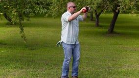 O jardineiro toma imagens e passeio no pomar de maçã filme