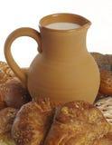 O jarro da argila com leite e as pastelarias fecham-se fotografia de stock