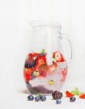 O jarro de vidro com bagas molha e cubos de gelo no fundo de madeira branco Imagens de Stock Royalty Free