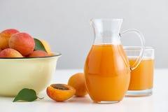 O jarro de vidro com suco fresco e os abricós maduros rolam Imagem de Stock