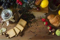 O jarro quente do chá em um fundo de madeira cercado no outono frutifica Imagens de Stock
