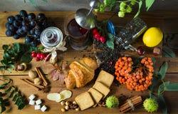 O jarro quente do chá em um fundo de madeira cercado no outono frutifica Foto de Stock Royalty Free