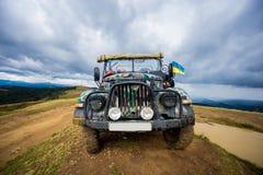 O jipe para a condução fora de estrada é sobre um monte nas montanhas Fotos de Stock Royalty Free
