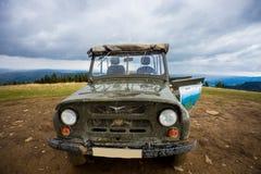 O jipe para a condução fora de estrada é sobre um monte nas montanhas Imagens de Stock Royalty Free