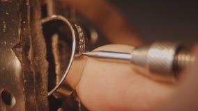 O joalheiro está ajustando uma pedra preciosa Fatura da joia do ofício Reparação do anel Pondo o diamante sobre o anel Macro Foto de Stock Royalty Free