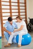 O joelho de Examining Senior Woman do terapeuta fotografia de stock