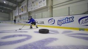 O jogador das crianças profissionais com controle da vara de hóquei o disco com obstáculos entre os pneumáticos dentro da pista d video estoque