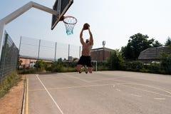 O jogador de basquetebol é aproximadamente ao afundanço Imagens de Stock