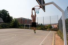O jogador de basquetebol é aproximadamente ao afundanço Fotografia de Stock Royalty Free