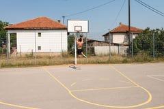 O jogador de basquetebol do halterofilista é aproximadamente ao afundanço Foto de Stock