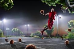 O jogador de basquetebol está dando certo na corte de noite Fotografia de Stock