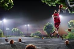 O jogador de basquetebol está dando certo na corte de noite Imagens de Stock
