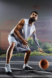 O jogador de basquetebol está dando certo na corte de noite Foto de Stock Royalty Free