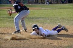 O jogador de beisebol da High School desliza na base foto de stock royalty free