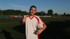 O jogador de futebol é dar os polegares-acima grandes, mostrando a como filme