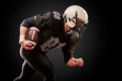 O jogador de futebol americano no uniforme escuro com a bola está preparando-se para atacar em um fundo preto foto de stock