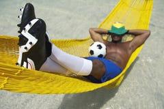 O jogador de futebol brasileiro relaxa com futebol na rede da praia imagens de stock royalty free