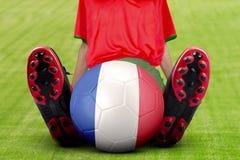 O jogador de futebol com bola senta-se no campo Imagens de Stock Royalty Free