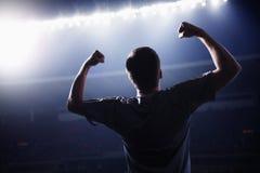 O jogador de futebol com braços levantou cheering, estádio na noite Imagens de Stock Royalty Free