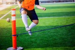 O jogador de futebol do menino executa brocas da coordenação e da força saltando sobre a corda no relvado artificial verde foto de stock