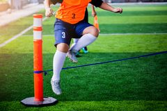 O jogador de futebol do menino executa brocas da coordenação e da força saltando sobre a corda no relvado artificial verde imagens de stock