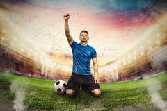 O jogador de futebol exulta em um estádio com audiência foto de stock