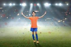 O jogador de futebol fêmea asiático feliz comemora Imagem de Stock