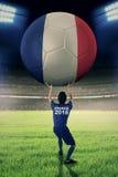 O jogador de futebol guarda a bola grande no campo Fotografia de Stock