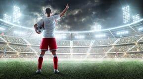 O jogador de futebol guarda uma bola de futebol no estádio profissional e a fala aos fãs Vista de atrás imagens de stock