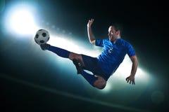 O jogador de futebol no meio do ar que retrocede a bola de futebol, estádio ilumina-se na noite no fundo Fotografia de Stock