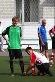 O jogador de futebol prende laços ao guarda-redes Imagem de Stock Royalty Free