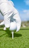 O jogador de golfe com luva branca coloc a esfera de golfe no T Imagem de Stock Royalty Free