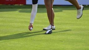O jogador de golfe est? empurrando a bola de golfe pelo clube de golfe das caixas do T no campo de golfe no jogo da competi??o imagem de stock royalty free