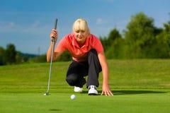 Jogador de golfe fêmea novo no curso que aponta para psto Fotografia de Stock Royalty Free