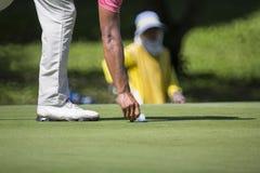 O jogador de golfe marca sua posição da bola sobre um verde Foto de Stock Royalty Free