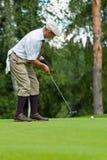 O jogador de golfe termina seu balanço imagens de stock