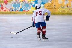 O jogador de hóquei com um disco no gelo da lâmina move o gelo fotografia de stock