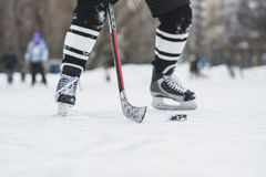 O jogador de hóquei corre com o disco no gelo Imagens de Stock Royalty Free