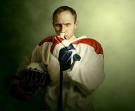 O jogador de hóquei em gelo do retrato no fundo do dramatick Imagens de Stock Royalty Free