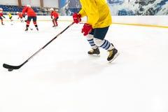 O jogador de hóquei em uma camiseta de alças amarela e em umas luvas vermelhas para povos conduz o disco O jogo do treinamento, o imagens de stock royalty free