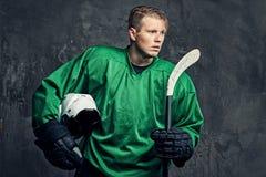 O jogador de hóquei profissional cansado em um sportswear verde guarda uma vara de hóquei e um capacete protetor em um fundo cinz foto de stock royalty free