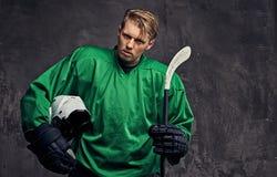 O jogador de hóquei profissional cansado em um sportswear verde guarda uma vara de hóquei e um capacete protetor em um fundo cinz fotografia de stock royalty free